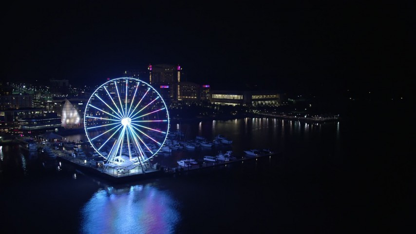 5K aerial video approaching Capitol Wheel, marina, and Gaylord National Resort and Convention Center, National Harbor, Maryland, night Aerial Stock Footage | AX77_016