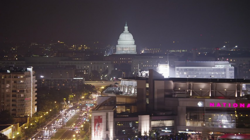 5K stock footage aerial video of the United States Capitol dome seen from S Capitol Street, reveal Nationals Park, Washington, D.C., night Aerial Stock Footage | AX77_023