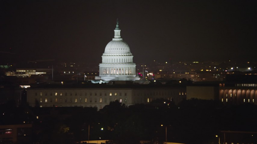5K stock footage aerial video of the United States Capitol behind House office building and James Madison Building in Washington, D.C., night Aerial Stock Footage AX77_027