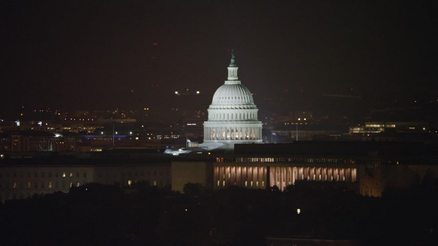 5K stock footage aerial video of United States Capitol dome behind James Madison Building in Washington, D.C., night Aerial Stock Footage | AX77_028