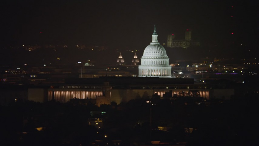 5K stock footage aerial video of United States Capitol behind Library of Congress buildings in Washington, D.C., night Aerial Stock Footage | AX77_029
