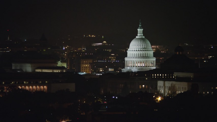 5K stock footage aerial video of the United States Capitol and Thomas Jefferson Building domes in Washington, D.C., night Aerial Stock Footage | AX77_030