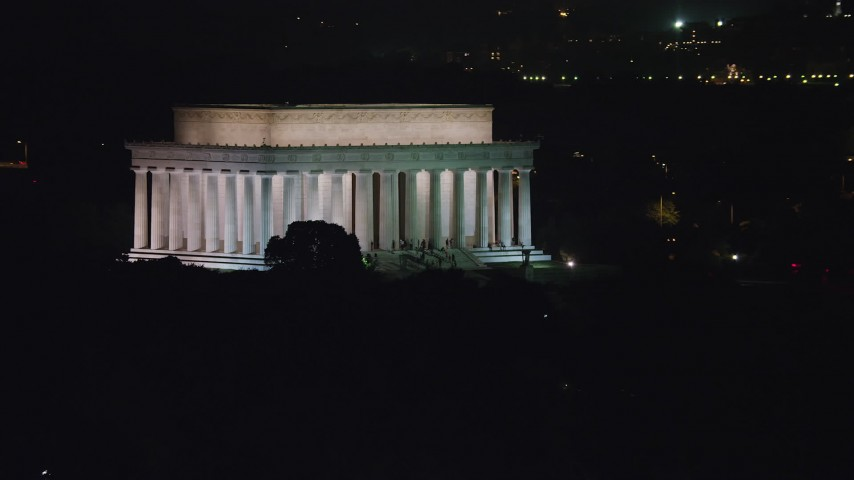 5K stock footage aerial video of the Lincoln Memorial with visitors on the steps in Washington, D.C., night Aerial Stock Footage | AX77_049