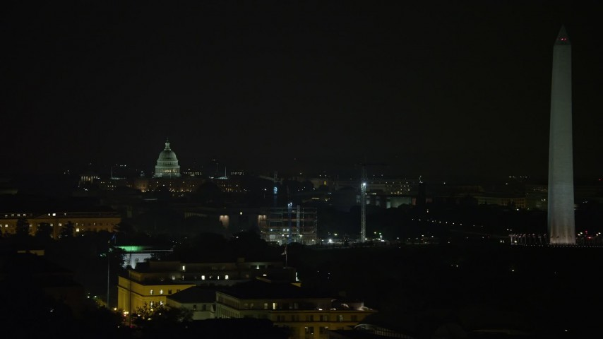 5K stock footage aerial video of the United States Capitol dome, construction cranes, and the Washington Monument, Washington, D.C., night Aerial Stock Footage | AX77_052