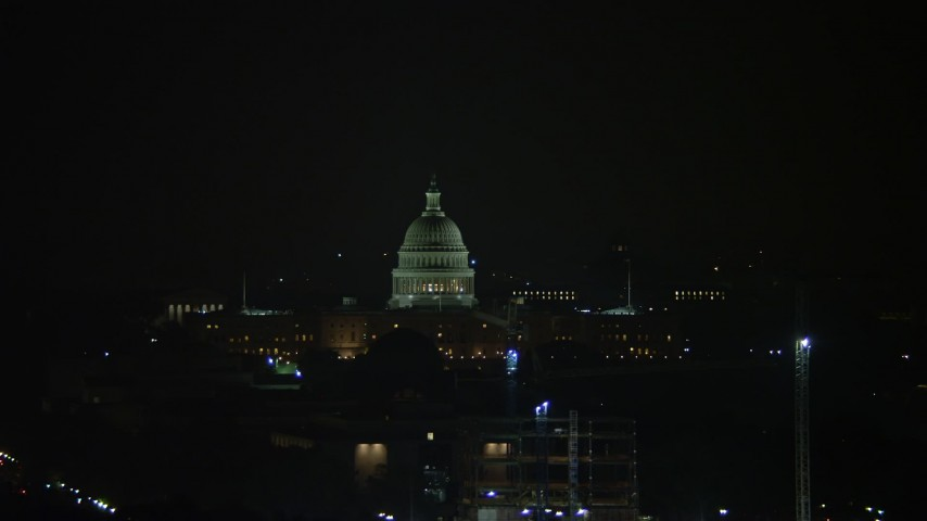 5K aerial video of the United States Capitol Building behind cranes in Washington, D.C., night Aerial Stock Footage | AX77_069