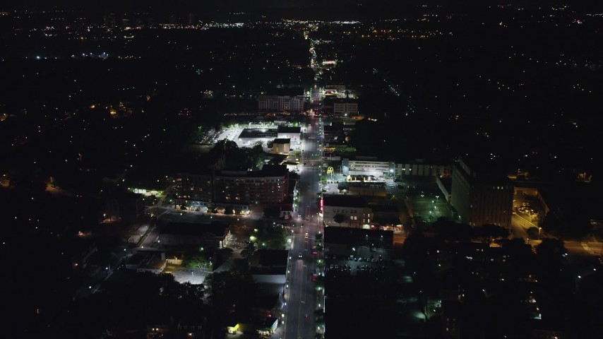 5K stock footage aerial video following Columbia Pike to approach a car dealership and shops in Arlington, Virginia, night Aerial Stock Footage | AX77_074