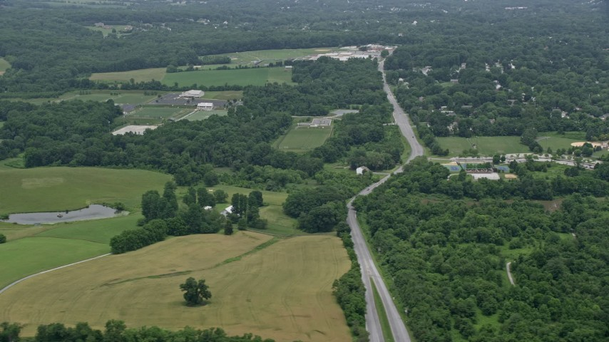 5K stock footage aerial video flying by farm fields in Ellicott City, Maryland Aerial Stock Footage | AX78_067E