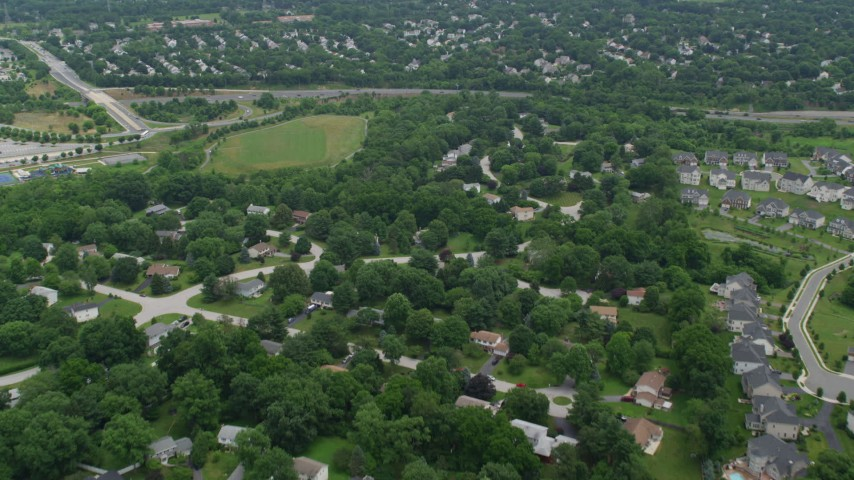 5K aerial video flying over suburban neighborhoods to approach Highway 100 in Ellicott City, Maryland Aerial Stock Footage | AX78_071