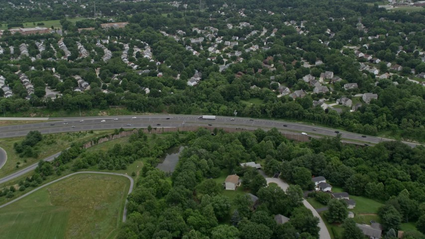 5K stock footage aerial video flying over suburban neighborhoods and Highway 100 to approach park in Ellicott City, Maryland Aerial Stock Footage | AX78_071E