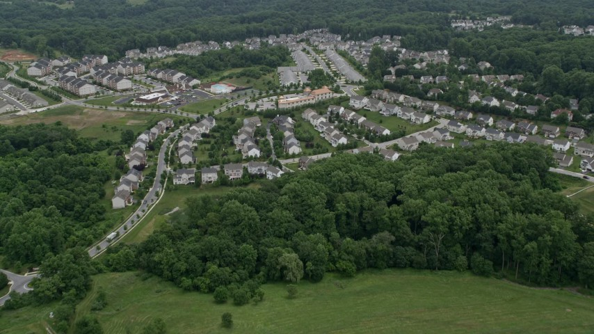 5K aerial video flying over Worthington Park and tract homes to approach Taylor Village Center and town homes in Ellicott City, Maryland Aerial Stock Footage AX78_073