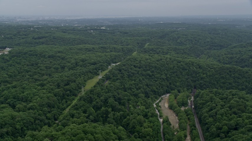 5K aerial video of a row of power lines through forest by Ellicott City, Maryland Aerial Stock Footage | AX78_075