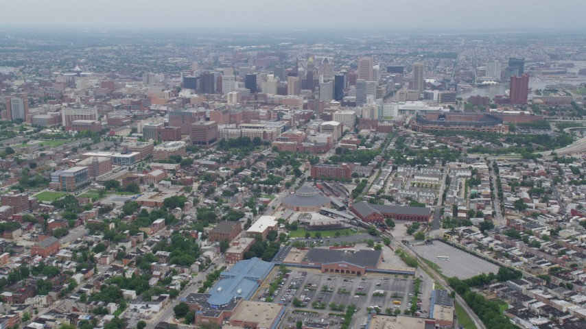 5K aerial video tilting from urban homes and streets to reveal and approach Downtown Baltimore skyscrapers, Maryland Aerial Stock Footage | AX78_084