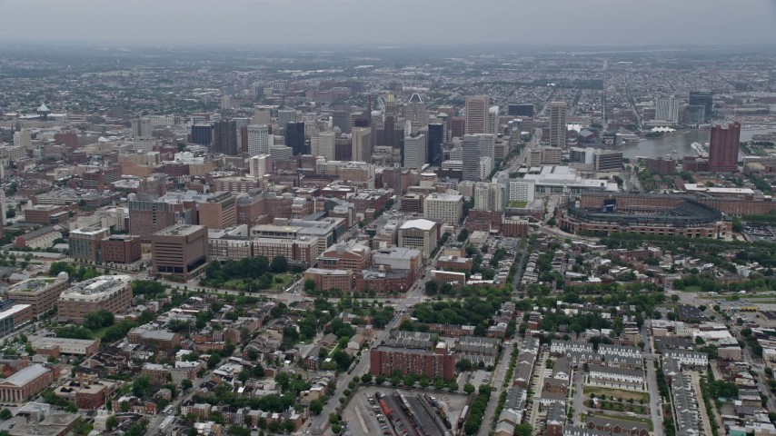 5K stock footage aerial video tilting from urban homes and streets to reveal and approach Downtown Baltimore skyscrapers, Maryland Aerial Stock Footage | AX78_084E