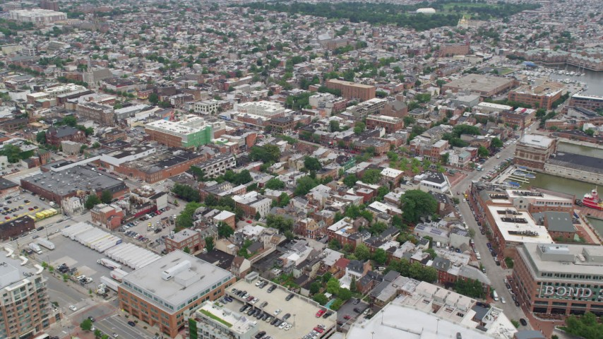 5K stock footage aerial video of shops and apartment buildings beside Broadway in Baltimore, Maryland Aerial Stock Footage | AX78_102