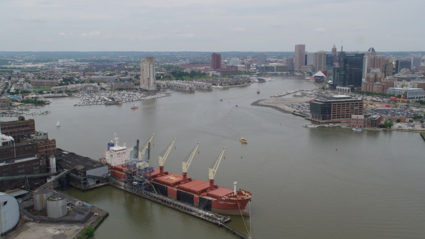 5K stock footage aerial video flying over cargo ship to approach Inner Harbor area of Downtown Baltimore, Maryland Aerial Stock Footage | AX78_106