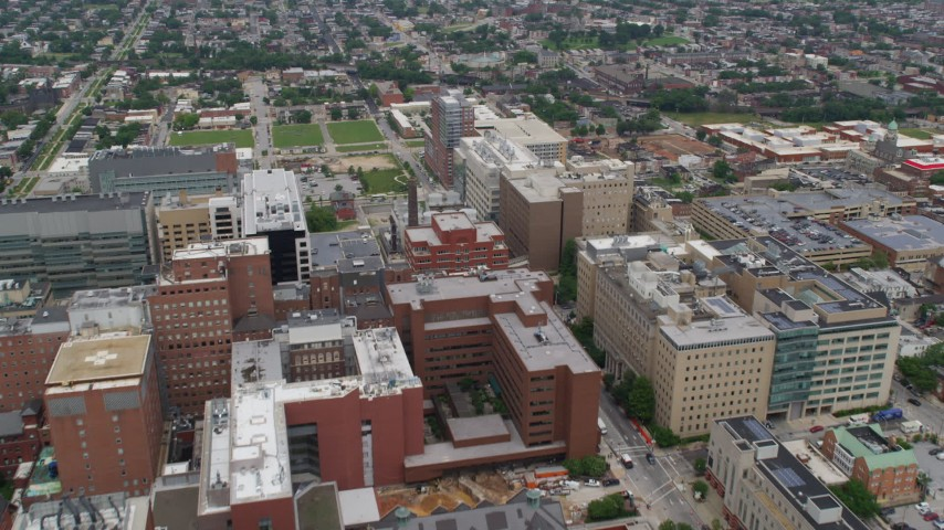 5K stock footage aerial video flying over Johns Hopkins Hospital buildings to approach urban neighborhoods in Baltimore, Maryland Aerial Stock Footage | AX78_117
