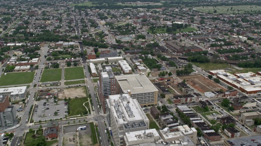 5K stock footage aerial video flying over Johns Hopkins Hospital buildings to approach urban neighborhoods in Baltimore, Maryland Aerial Stock Footage | AX78_117E