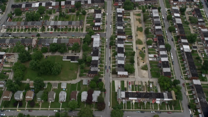 5K aerial video tilting from urban row houses, tilt up revealing Herring Run Park, public housing in Baltimore, Maryland Aerial Stock Footage AX78_122