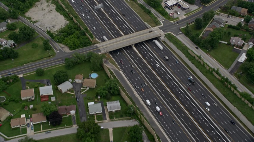 5K aerial video tilting from a bird's eye of light traffic on Interstate 95 in Baltimore, Maryland, to reveal suburban neighborhoods Aerial Stock Footage | AX78_125