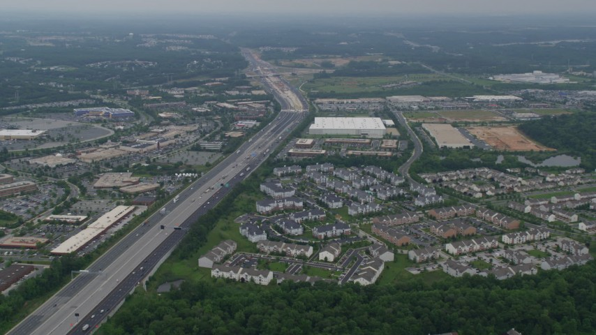 5K aerial video approaching offices, mall, light traffic on Interstate 95, apartment buildings in Baltimore, Maryland Aerial Stock Footage | AX78_129