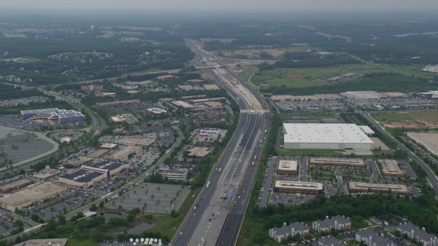 5K aerial video flying over light traffic on Interstate 95 between The Avenue at White Marsh mall and a warehouse in Baltimore, Maryland Aerial Stock Footage | AX78_130