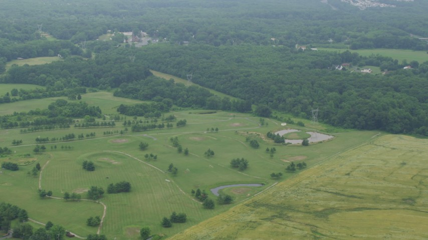 5K stock footage aerial video flying over golf course to approach power lines in Kingsville, Maryland Aerial Stock Footage | AX78_136