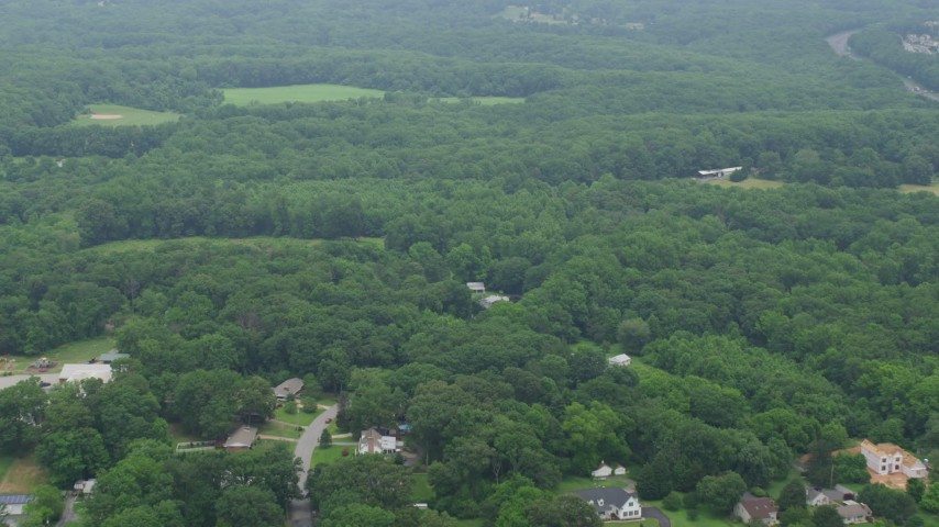5K stock footage aerial video flying over forest and rural homes to approach a grassy field in Kingsville, Maryland Aerial Stock Footage | AX78_138