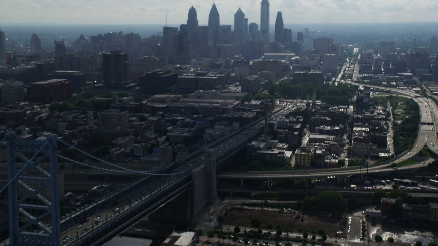 5K stock footage aerial video tilting from Benjamin Franklin Bridge to reveal skyline of Downtown Philadelphia, Pennsylvania Aerial Stock Footage | AX79_004