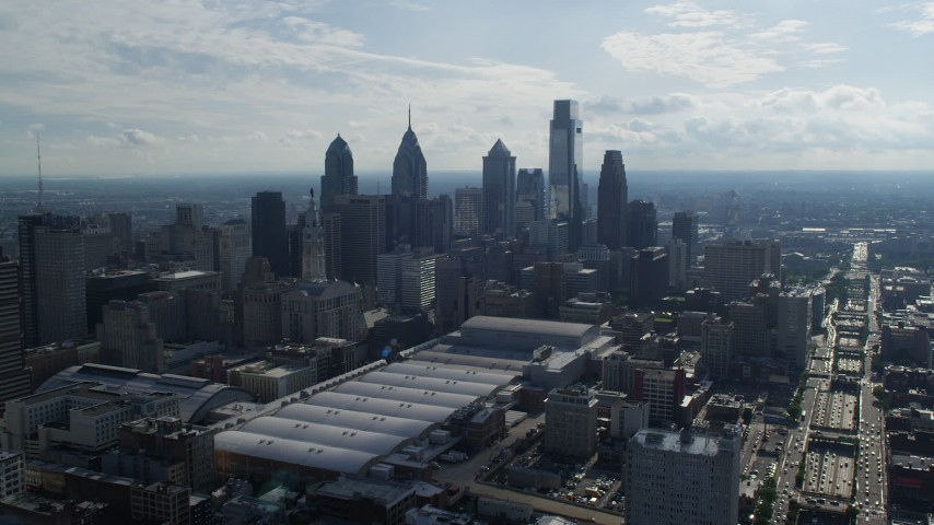 5K stock footage aerial video flying over convention center, approaching city hall and skyscrapers in Downtown Philadelphia, Pennsylvania Aerial Stock Footage | AX79_037