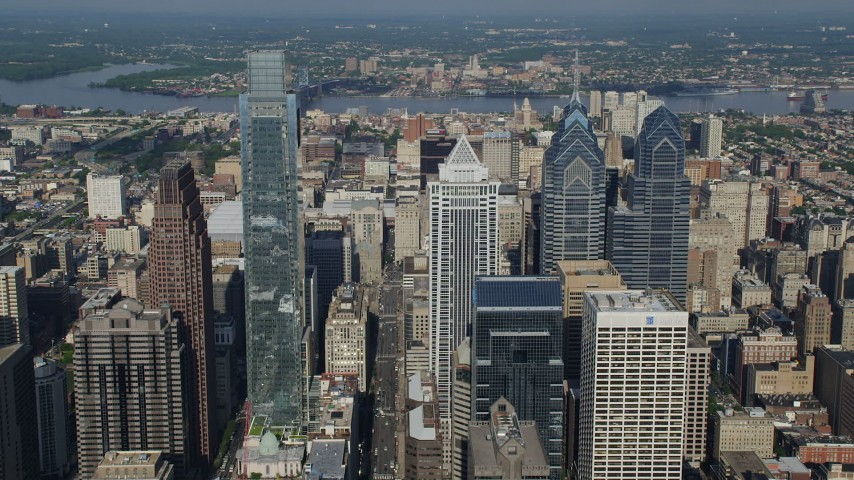5K stock footage aerial video flying over BNY Mellon Center to reveal City Hall and convention center in Downtown Philadelphia, Pennsylvania Aerial Stock Footage | AX79_054