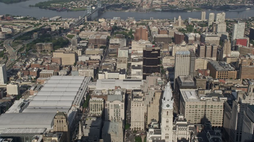 5K aerial video flying over convention center and office buildings, approaching Benjamin Franklin Bridge, Downtown Philadelphia, Pennsylvania Aerial Stock Footage | AX79_055