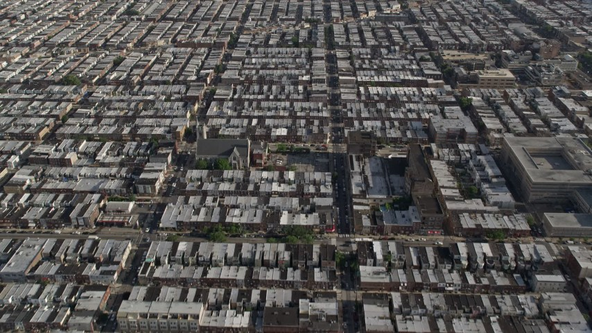 5K stock footage aerial video following S 12th Street through urban neighborhoods in South Philadelphia, reveal sports fields, Pennsylvania Aerial Stock Footage | AX79_075E