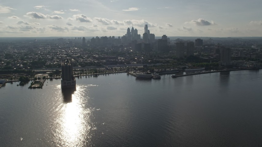 5K stock footage aerial video flying over Delaware River to approach Downtown Philadelphia skyline, Pennsylvania Aerial Stock Footage | AX79_096