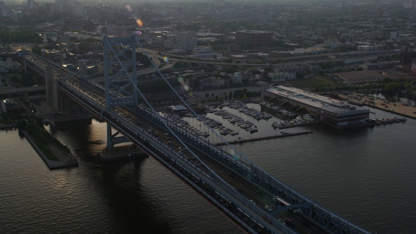 5K stock footage aerial video of the Benjamin Franklin Bridge beside a marina in Philadelphia, Pennsylvania, Sunset Aerial Stock Footage | AX80_003