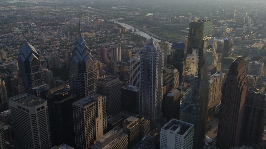 5K aerial video flying over BNY Mellon Center to approach the Schuylkill River, Downtown Philadelphia, Pennsylvania, Sunset Aerial Stock Footage | AX80_008