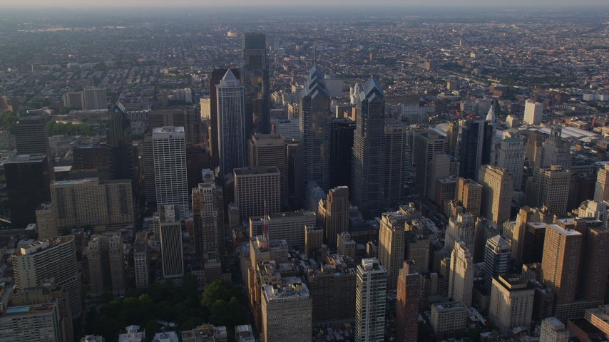 5K aerial video approaching One and Two Liberty Place and skyscrapers in Downtown Philadelphia, Pennsylvania, Sunset Aerial Stock Footage | AX80_012