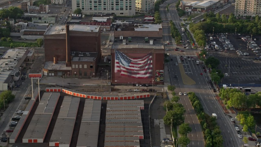 5K stock footage aerial video of an American flag mural on a warehouse building in Philadelphia, Pennsylvania, Sunset Aerial Stock Footage | AX80_030