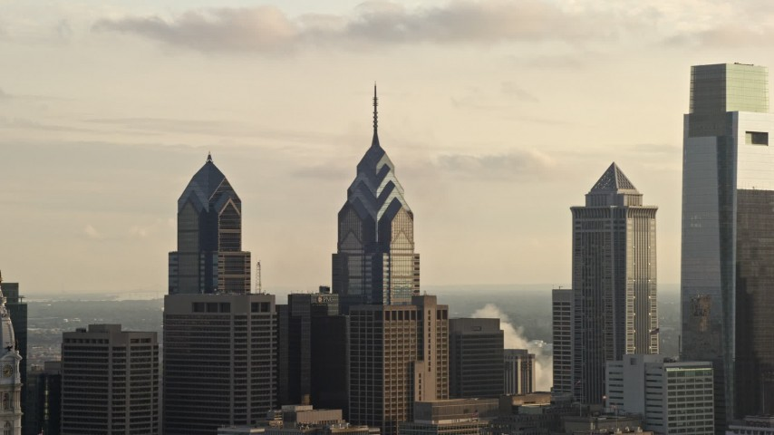 5K aerial video of rooftops of One and Two Liberty Place, Philadelphia, Pennsylvania, Sunset Aerial Stock Footage | AX80_032