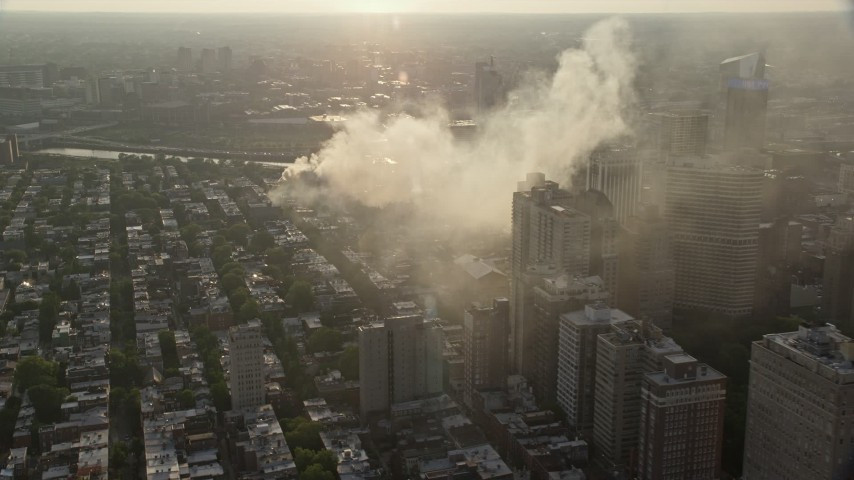 5K stock footage aerial video of residential fire near office buildings in Downtown Philadelphia, Pennsylvania, Sunset Aerial Stock Footage   AX80_035E