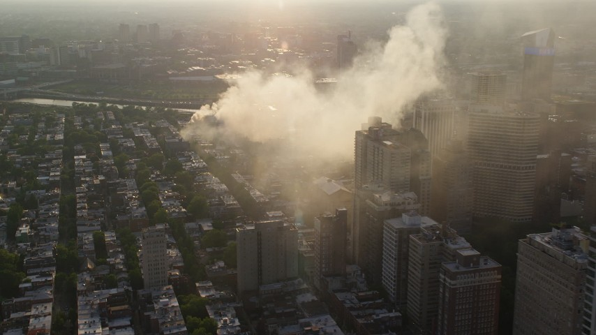 5K stock footage aerial video of smoke rising from a residential fire near Downtown Philadelphia, Pennsylvania, Sunset Aerial Stock Footage | AX80_036