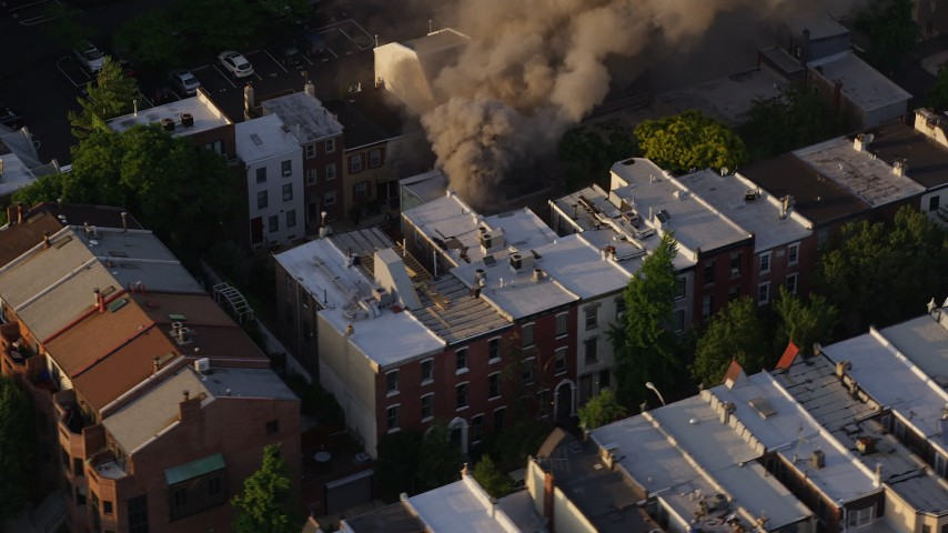 5K aerial video of smoke from a residential fire near Downtown Philadelphia, Pennsylvania, Sunset Aerial Stock Footage | AX80_038