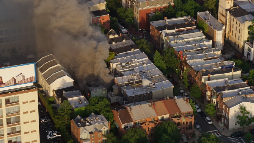 5K stock footage aerial video of smoke and flames at a residential fire near Downtown Philadelphia, Pennsylvania, Sunset Aerial Stock Footage | AX80_039