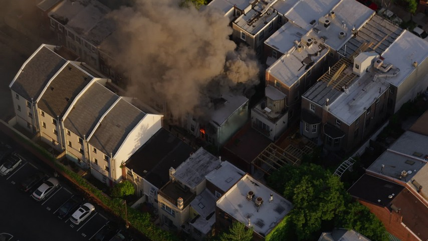 5K stock footage aerial video tilting to a bird's eye view of smoke and fire from an urban home in Philadelphia, Pennsylvania, Sunset Aerial Stock Footage | AX80_040