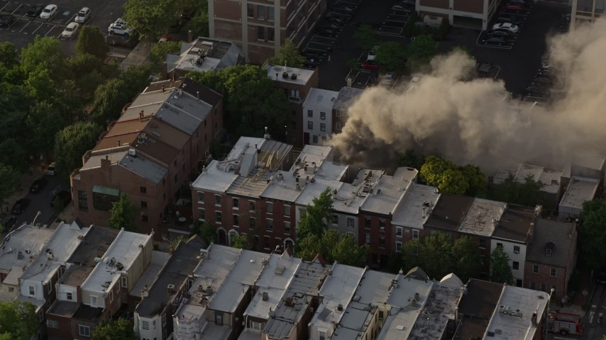 5K stock footage aerial video of a reverse view of a residential fire near Downtown Philadelphia, Pennsylvania, Sunset Aerial Stock Footage | AX80_041
