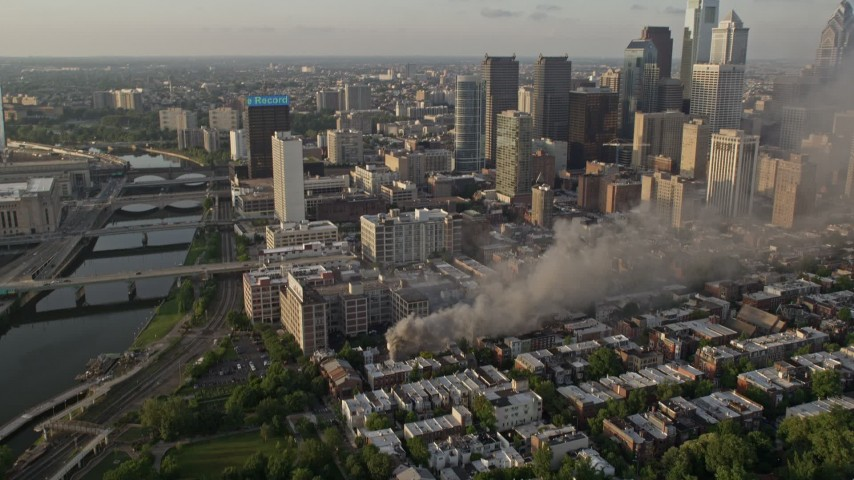 5K stock footage aerial video of residential fire by the Downtown Philadelphia skyline, Pennsylvania, Sunset Aerial Stock Footage | AX80_042