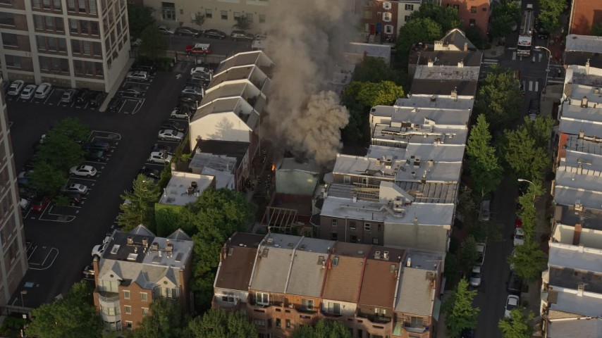 5K stock footage aerial video tracking a residential fire near Downtown Philadelphia, Pennsylvania, Sunset Aerial Stock Footage | AX80_043