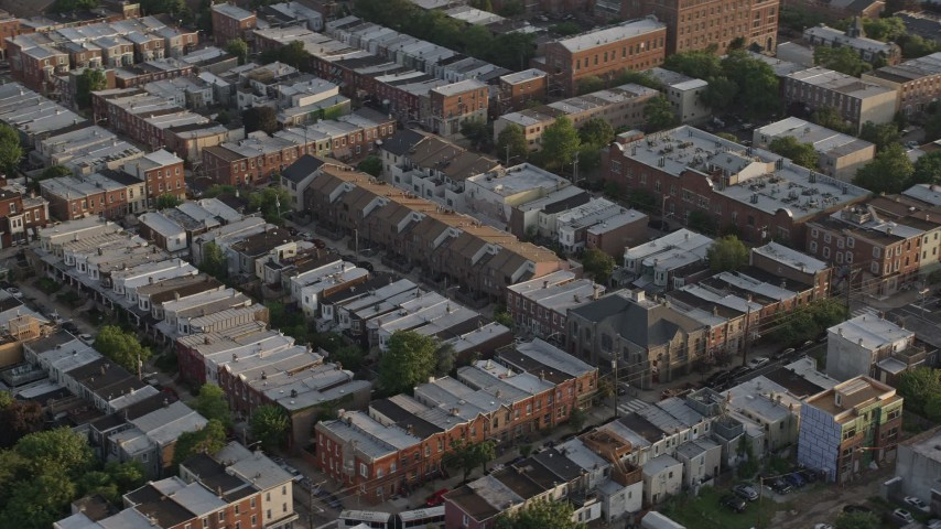 5K stock footage aerial video flying by row houses in North Philadelphia, Pennsylvania, Sunset Aerial Stock Footage | AX80_052