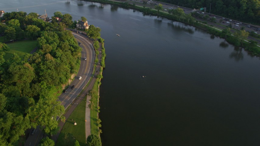 5K stock footage aerial video panning across the Schuylkill River to reveal Boathouse Row, Philadelphia, Pennsylvania, Sunset Aerial Stock Footage | AX80_054