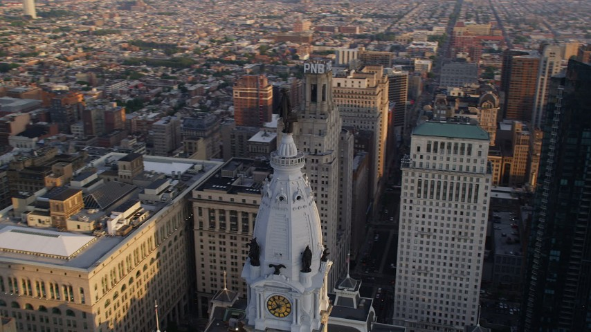 5K stock footage aerial video tracking the William Penn statue on Philadelphia City Hall, reveal Downtown Philadelphia skyscrapers, Pennsylvania, Sunset Aerial Stock Footage | AX80_058
