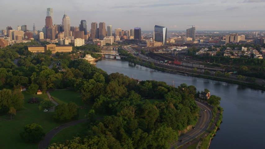 5K stock footage aerial video of Downtown Philadelphia skyline seen from Boathouse Row and the the Schuylkill River, Pennsylvania, Sunset Aerial Stock Footage | AX80_065